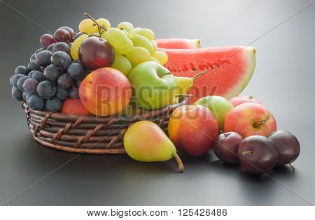 Various fresh ripe fruits arranged in a wicker basket and around on neutral gray gradient background