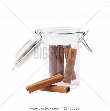 Glass jar filled with the cinnamon sticks isolated over the white background