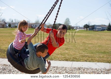 Three siblings playing on a tire swing outside on a spring day.