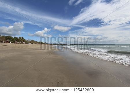 Kuta beach Bali Indonesia. Indian ocean with waves and blue sky with clouds.
