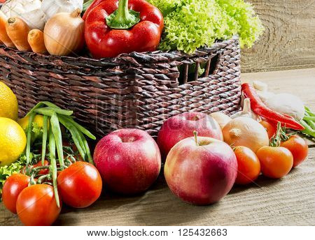 wicker basket with many fruits and vegetables on wooden table