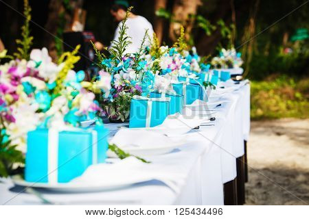 Laid wedding table with gifts and flowers