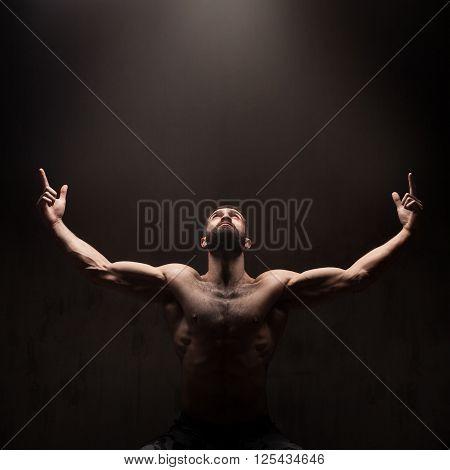 Man praying on dark studio background. Dramatic light from above
