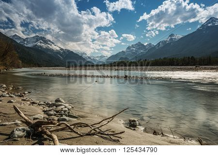 sand bank and stony river lech at tirol mountains with blue sky