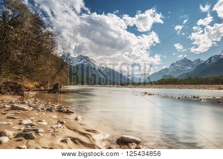 sandy and stony river bank with cold water in austrian mountain valley