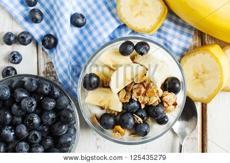 Yogurt with homemade granola banana and blueberries. Healthy breakfast.