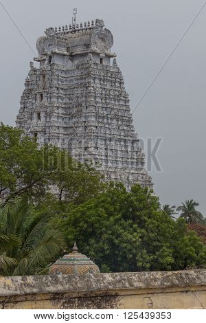 Trichy India - October 15 2013: The dirty-white Vellai Gopuram at the Sri Ranganathar Swamy sanctuary towers over green trees against a rain-filled gray sky.