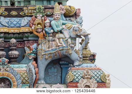 Trichy India - October 15 2013: Closeup of decoration on one Gopuram at Shirangam temple. Three people riding an elephant. One royal. Pastel colors gray sky.