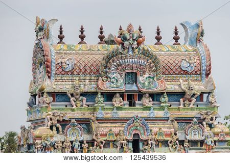 Trichy India - October 15 2013: Top of the gopuram called Vimanam shaped as a cake with plenty of statues in pastel colors. Garudas on corners.