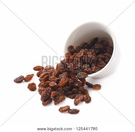 White ceramic cup filled with multiple raisins isolated over the white background