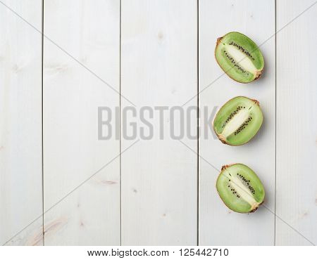 Three sliced halves of kiwi fruit or chinese gooseberry kiwi over the white wooden board surface