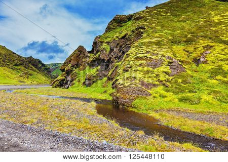 Picturesque basalt hills covered with green grass and moss. Streams from melting glaciers flowing down the canyon. Canyon Pakgil in Iceland