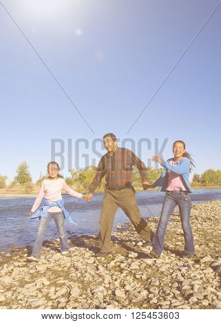 Mongolian Family Enjoy Walking by The River Concept