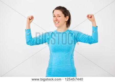 Young woman during some fitness, blue top shoot over white wall