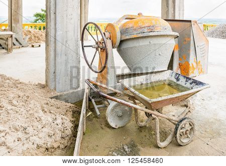 Old Cement mixer machine with sand truck stop beside at a construction site.