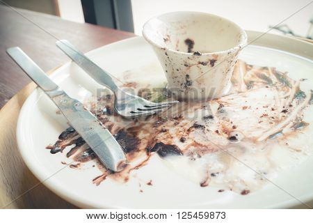 Empty and dirty white plate and cup after eating dessert (Vintage effect)