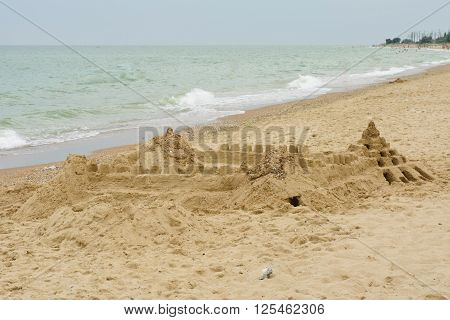 Grand sand castle on an empty beach.