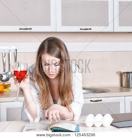 girl in a white men's shirt drinking red wine and reading a book in the kitchen. close-up