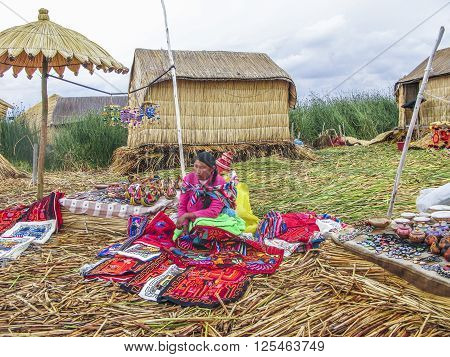 PUNO PERU JAN 20 2015: Uros islands on Titicaca lake - Local women in traditional attire work sell handicrafts to tourists in Puno Peru.