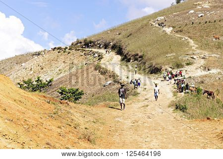 FOND BAPTISTE, HAITI - FEBUARY 18, 2016 - A wide view multiple people walking towards a weekly market (market not in view).