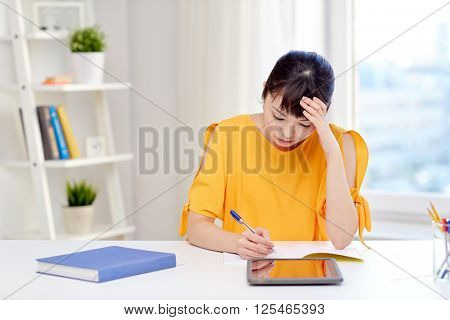 people, education, high school and learning concept - tired or bored asian young woman student with tablet pc computer, book and notepad writing at home