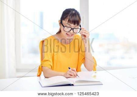people, education, high school and learning concept - happy asian young woman student in glasses reading book and writing to notepad at home