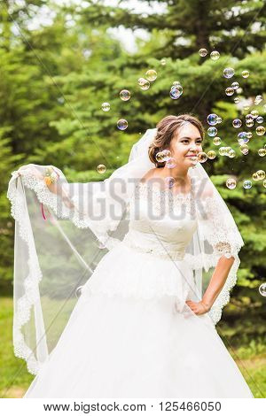 Young bride play with soap-bubble and joy smile.