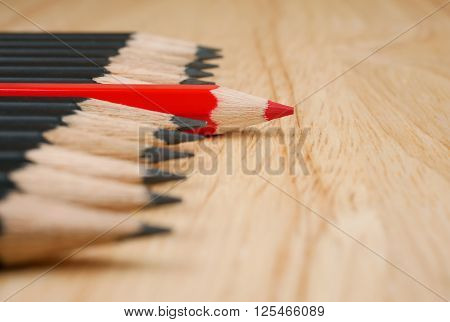 Red pencil standout from black pencil leadership business concept