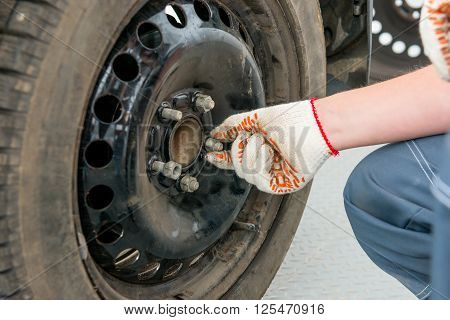Hand In A Glove Unscrews The Nuts On The Wheel