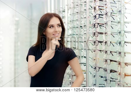 Woman Choosing Eyeglasses Frames in Optical Store - Cute girl deciding for glasses of different shapes and colors poster