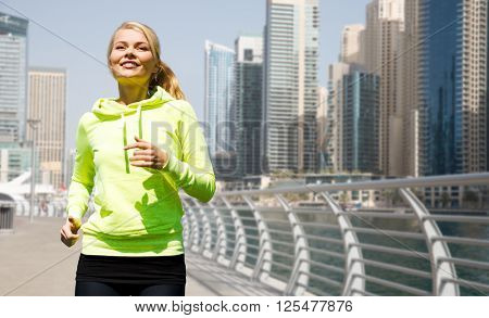 fitness, sport, people and healthy lifestyle concept - happy young woman jogging over dubai city street or waterfront background