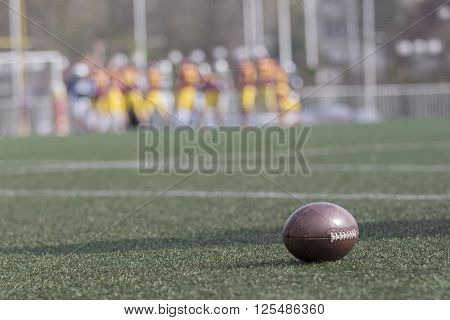 Ball on green grass American football field and blurred players in the background