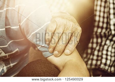 grandfather's hand holding young arm of nephew