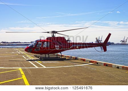 New York, USA - April 25, 2015: Red Helicopter on the helipad in Lower Manhattan in New York USA on East River. Pier 6.
