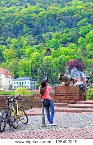 HEIDELBERG GERMANY - MAY 5 2013: Tourists near Bridge mandrill on Old bridge in Heidelberg in Germany