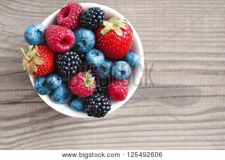 Ripe sweet different berries in bowl. Close up top view high resolution product. Harvest Concept