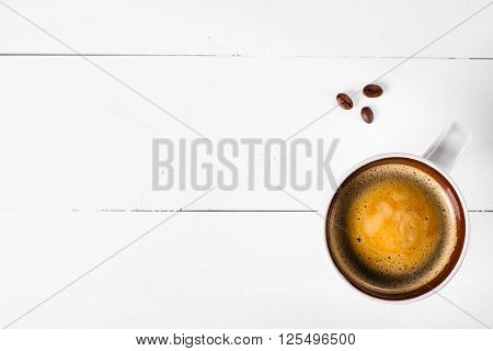 Coffee cup top view on white wooden table background. Flat lay cup of coffee and three coffee beans. Copy space.