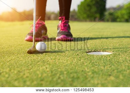 Golfer putting on green for birdie while on vacation