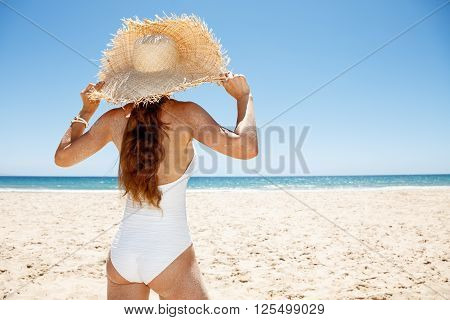 Seen From Behind Woman In White Swimsuit And Straw Hat At Beach