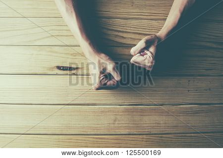 Female fists clenched on a wooden table in anger