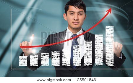 Unsmiling businessman holding against red arrow