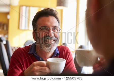 Male couple drink coffee at a restaurant, over shoulder view