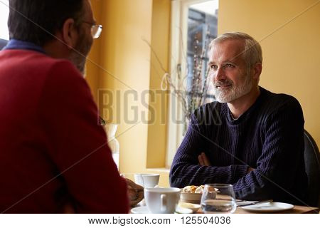 Middle aged gay male couple having lunch in a restaurant