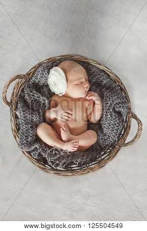 Newborn baby with white flower on head, sleeping sweetly in the brown, round, wicker basket in soft grey knitted shawl,pursing his arms and legs,a portrait of a sleeping baby on grey background