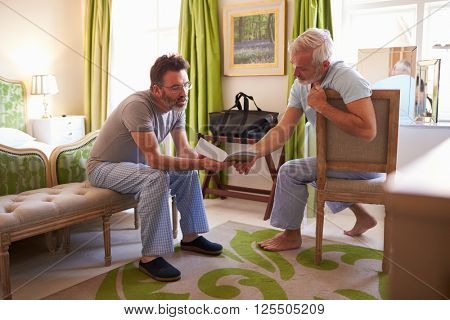 Male couple wearing pyjamas in a hotel room plan their day