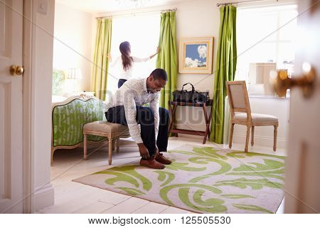 Young multi ethnic couple getting ready in a hotel room