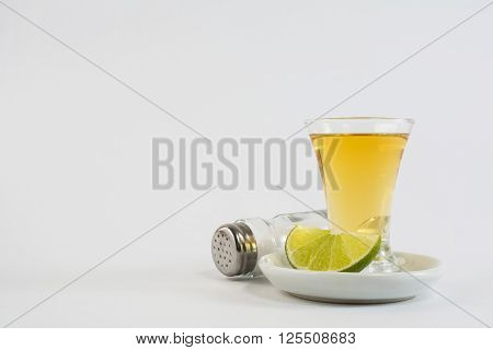 Tequila shot with lime and salt on white background. Gold Mexican tequila. Tequila