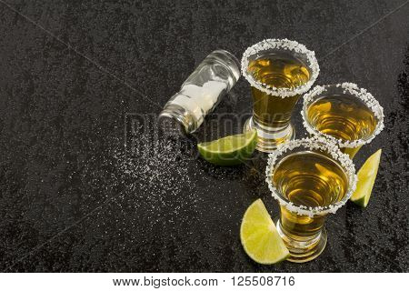 Tequila shots with lime and salt on black table. Tequila. Gold Mexican tequila