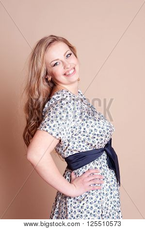 Laughing woman 20-25 year old posing in room over beige. Wearing dress with floral print. Looking at camera. Young adults.