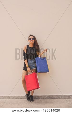 Fashionista with many paper-bags standing at the wall